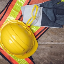Flat lay image with a hard hat, high vis vest and safety equipment