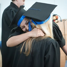 Two female graduates hugging