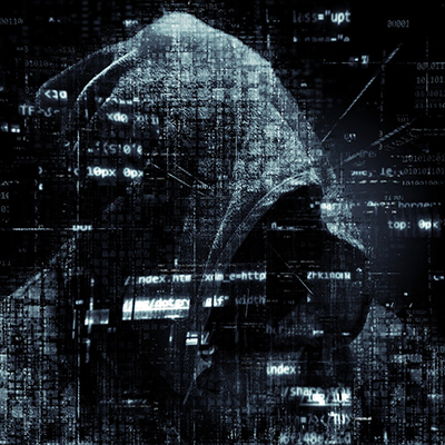 A hooded figure in the background with computer code across the forefront of the image