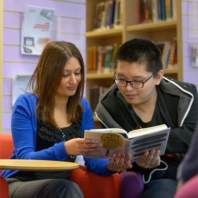 Member of Library staff with student looking at a book
