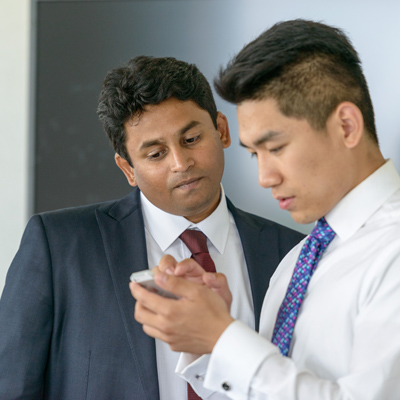 Two men looking at smartphone