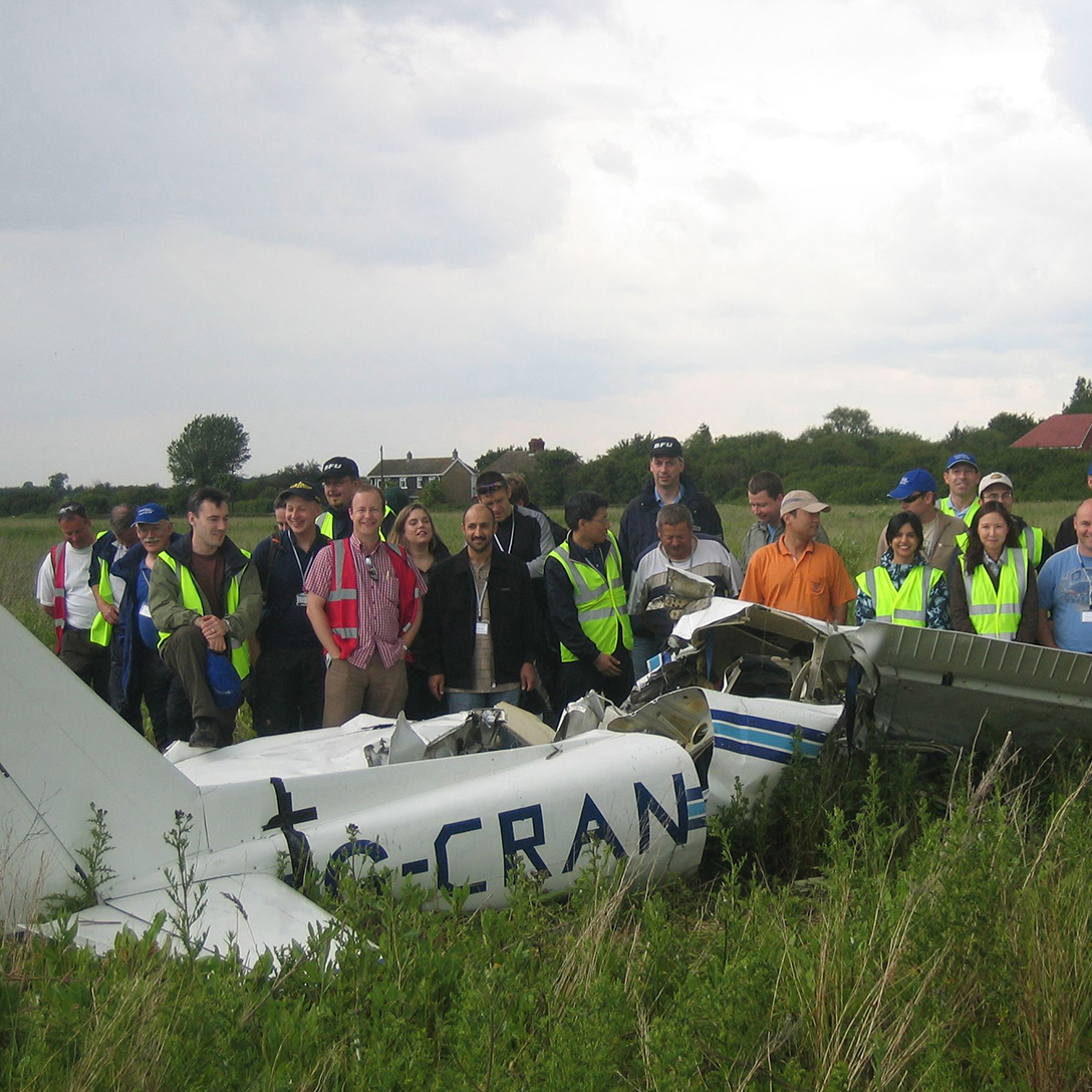 People stood by plane wreckage