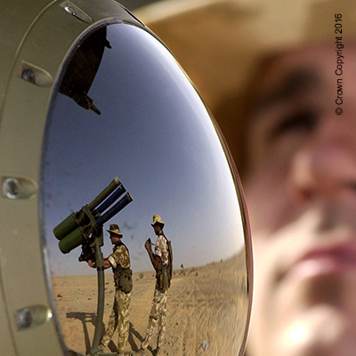 mirror reflection of soldiers loading gun missiles