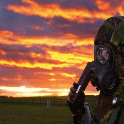 Military man in mask with radio against sunset